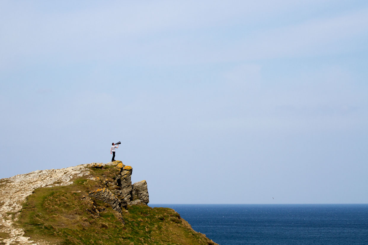 man standing on cliff shouting through a loud hailer