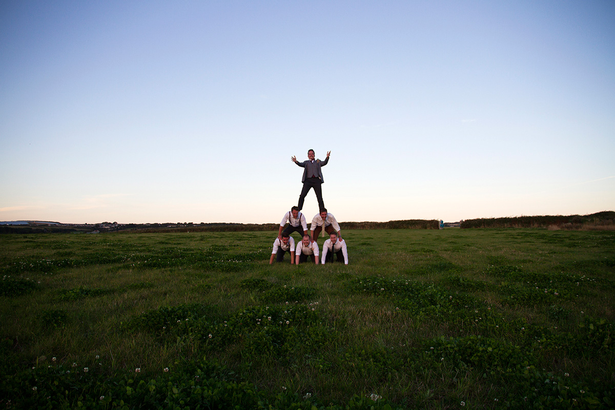 human pyramid in a field at sunset