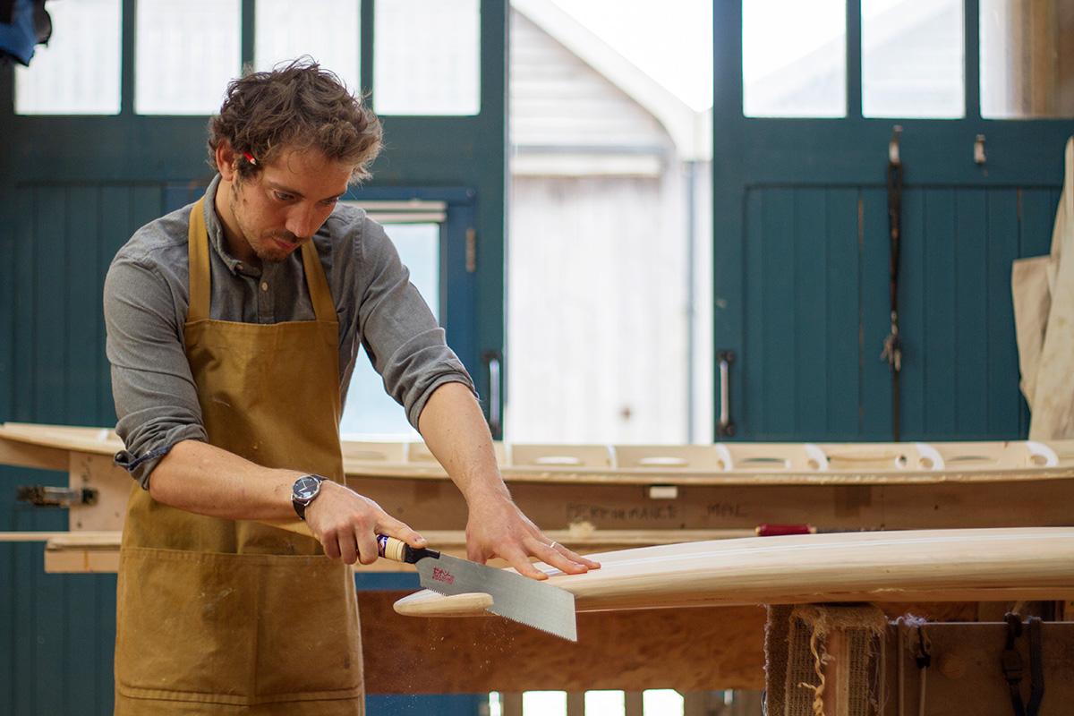 wooden surfboard maker james otter cutting the tail block of a surfboard in his workshop in cornwall