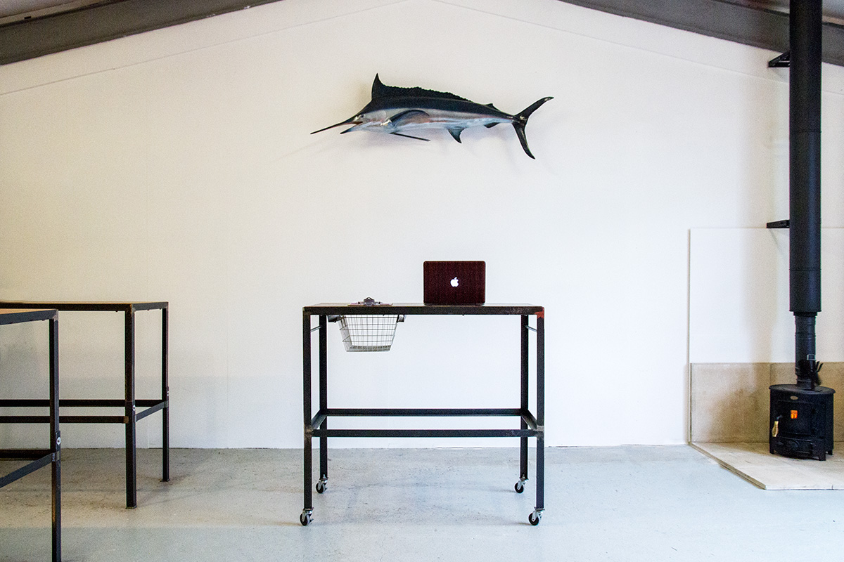 a standing desk at the hailer creative content studio in st agnes, cornwall, with a marlin on the wall above it and a woodburning stove in the corner of the room