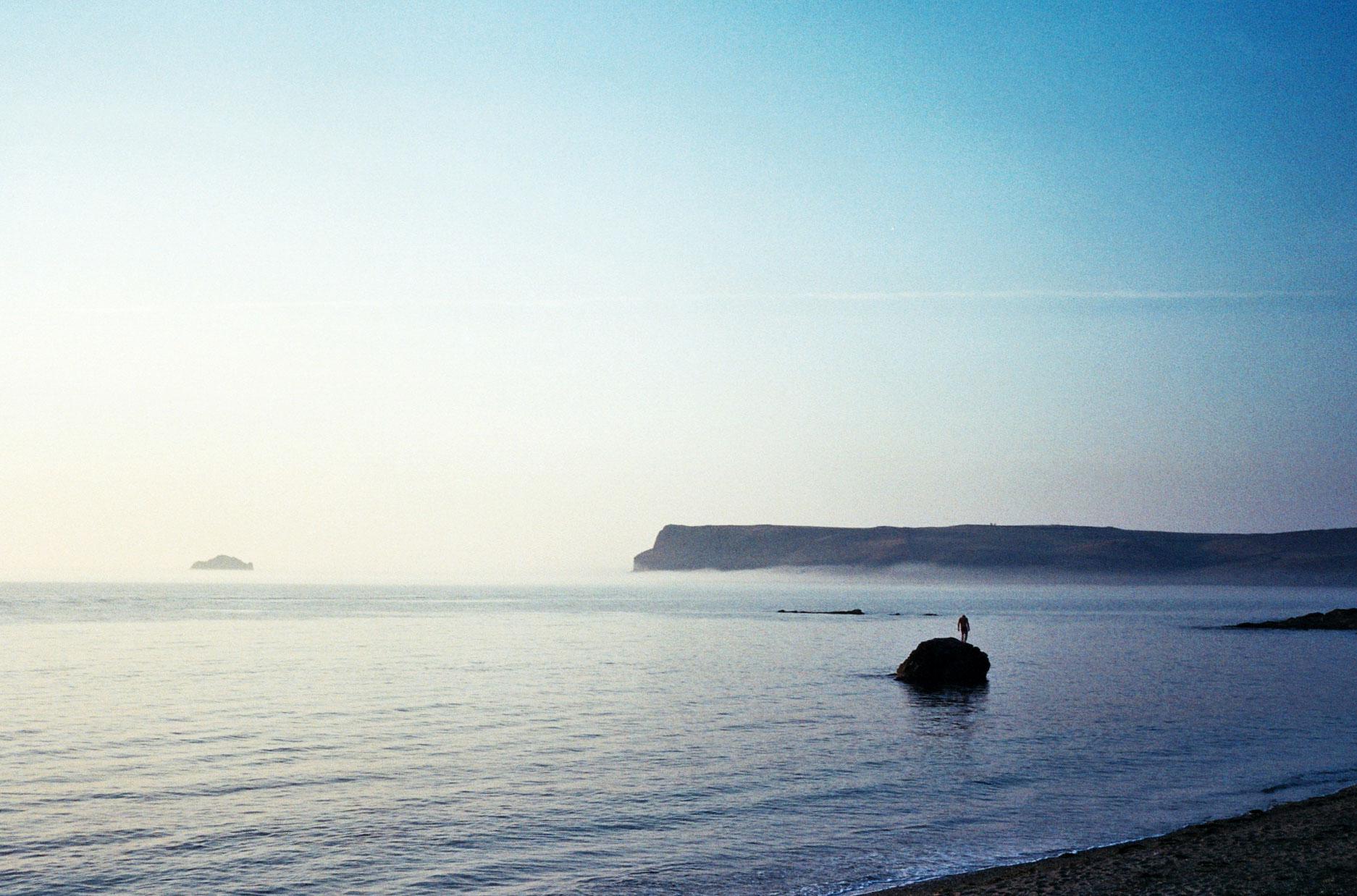 lone man stood on rock in sea