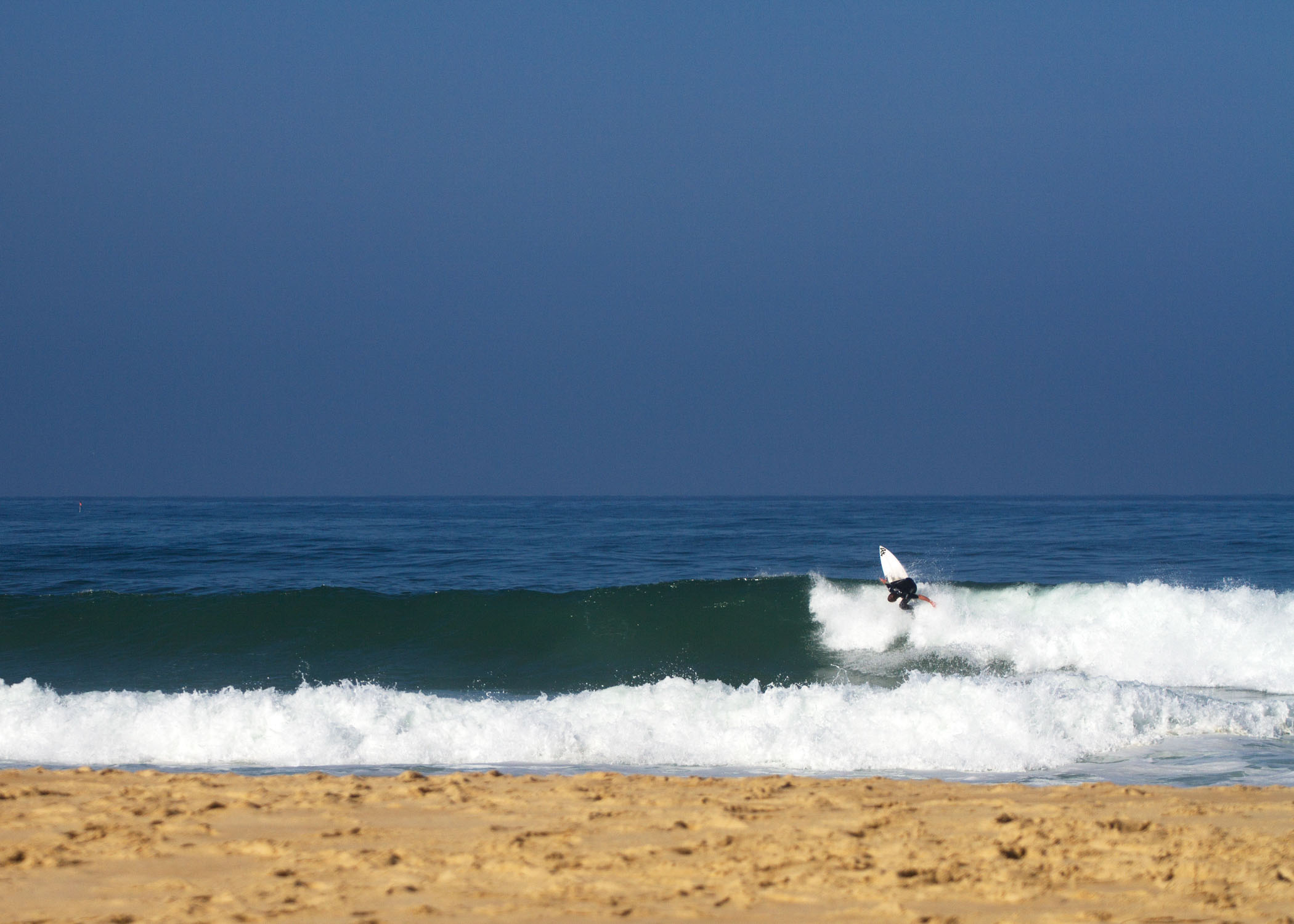 surf simply coach performing a backhand foam climb on a wave in france