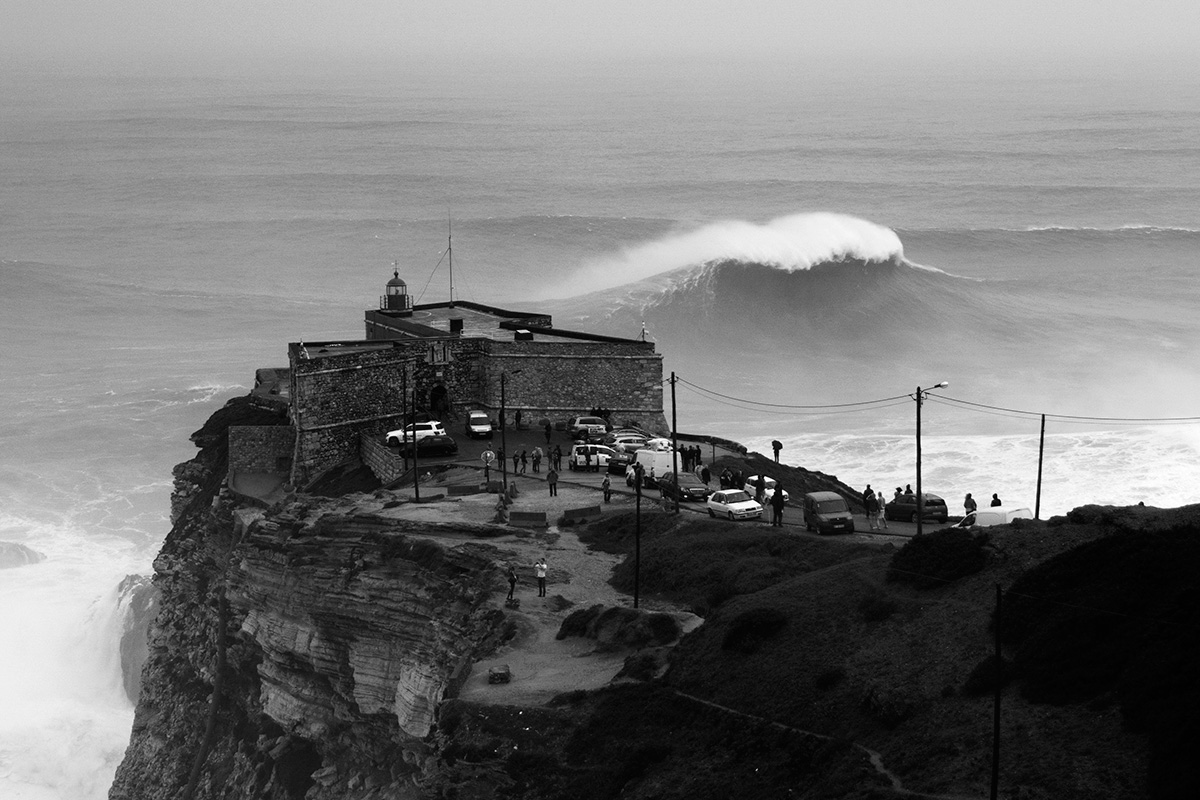 big waves breaking in front of the lighthouse at nazare in portugal photographed by mat arney